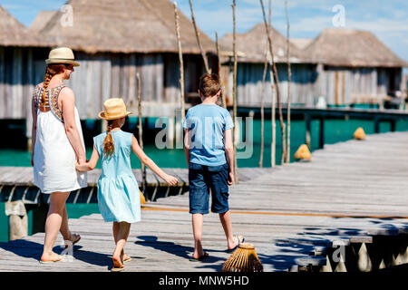 Back view of happy beautiful family walking on wooden jetty during summer vacation at luxury resort - Stock Photo