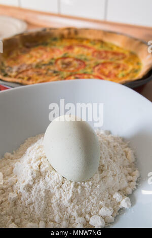 fresh quiche with green eggs, tomatos and spring onions - Stock Photo