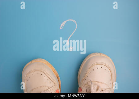 sneaker on blue background Surrounded by question marks - Stock Photo