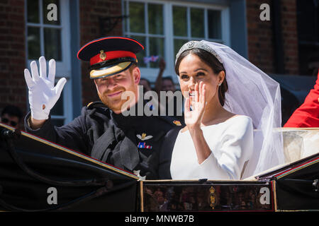 Windsor, UK, 19 May 2018. Prince Harry and his bride Meghan Markle ride around the streets of Windsor in a state Landau greeted by huge crowds cheering and waving flags following their wedding at St Georges Chapel. Before heading back to Windsor castle for their wedding reception. They will now be know as The Duke and Duchess of Sussex - Stock Photo