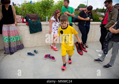 Sofia, Bulgaria. 19th May, 2018. Yavor Milchov, 7, and his sister, Ranya, 9, tried on high-heeled shoes during the ''Walk a Mile in Her Shoes'' campaign, which was held in Sofia to draw attention to the violence against women and to show solidarity with the problems women face. Credit: Jodi Hilton/SOPA Images/ZUMA Wire/Alamy Live News - Stock Photo