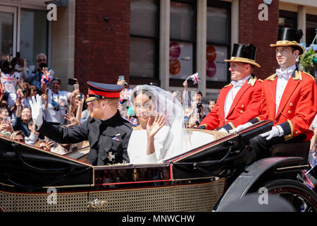Windsor, UK, 19 May 2018. Royal Wedding. Prince Harry marries Meghan Markle.  Following their marriage at St Georges Chapel in the grounds of Windsor Castle, the newly titled HRH Prince Harry, Duke of Sussex and Meghan, Duchess of Sussex wave to the crowd during a procession through Windsor in the Ascot Landau carriage. 19th May, 2018. Windsor, England. Credit: amanda rose/Alamy Live News - Stock Photo