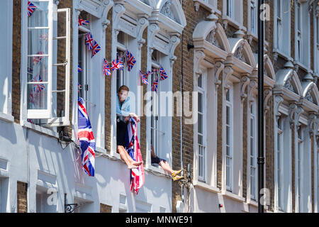 Royal Wedding. Royal fans sit in windows to look onto the wedding procession route of HRH Prince Harry and Meghan Markle. 19th May, 2018. Windsor, England. - Stock Photo