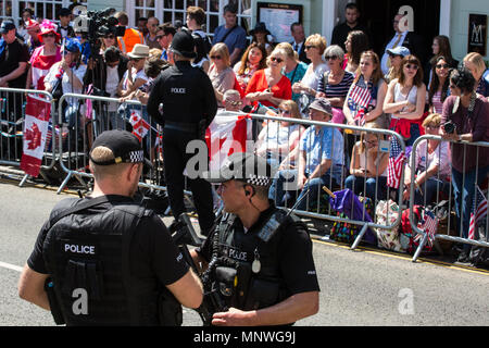 Windsor, UK. 19th May, 2018. Armed police officers patrol in front of thousands of well-wishers lining the streets of Windsor to witness the carriage procession of Prince Harry and Meghan Markle, now the Duke and Duchess of Sussex following their wedding at St George's Chapel in Windsor Castle. Credit: Mark Kerrison/Alamy Live News - Stock Photo