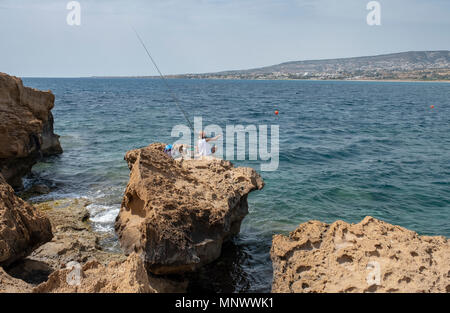 A man fishing from the rocks in the Coral Bay area, near Paphos, Cyprus - Stock Photo