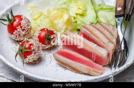 Grilled tuna with spice, cherry tomatoes, sesame and lettuce in a plate on the table. Gourmet dinner. Selective focus - Stock Photo