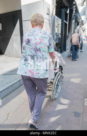 Old women pushing another women in a wheel chair, antwerp, belgium - Stock Photo