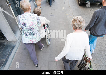 Old women pushing another women in a wheel chair, antwerp, belgium - Stock Photo