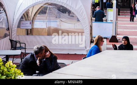 Couple kissing in the outside area of the British Library while two women talk in the background. London, England, UK - Stock Photo