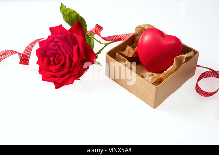 Rose red flower with green leaves and stem and a beige small gift box with a heart and ribbon on a white background - Stock Photo