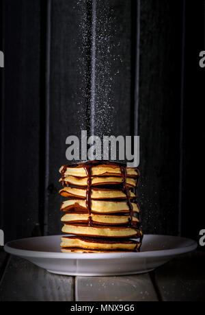 Fresh and delicious sweet pancakes with falling sugar on top, and chocolate syrup sauce - Stock Photo