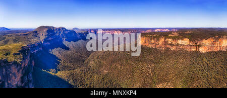 Lit by warm sun light on steep sandstone rock walls forming the Grand Canyon in Australian Blue mountains - wide aerial panorama. - Stock Photo