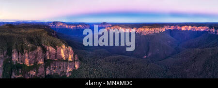 Majestic Blue Mountains at sunset in elevated panorama around eroded sandstone cliff called Pulpit rock and surrounding grand canyon ranges. - Stock Photo