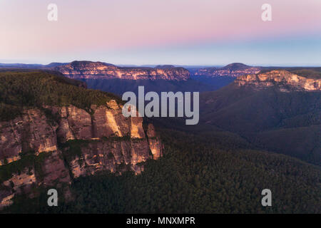 Blue Mountains Grand Canyon from GOvett leap with Pulpit rock cliffs at sunset in elevated aerial view towards pink sky. - Stock Photo