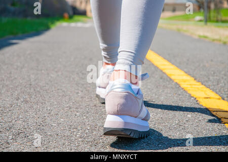 Walking. Close-up of women's running shoes on a paved trail. Female feet in sneakers. - Stock Photo