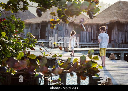 Kids brother and sister walking on wooden footbridge during summer vacation at luxury resort - Stock Photo