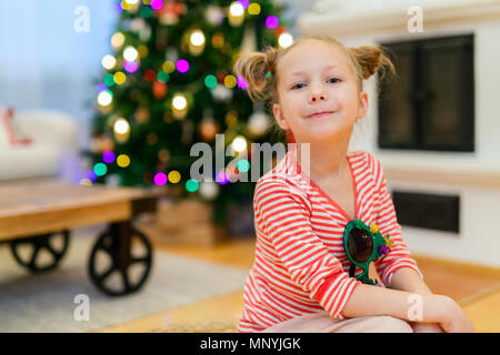 Adorable little girl at home beautifully decorated for Christmas with fireplace,  tree,  stockings and lights - Stock Photo