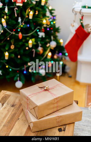 Christmas presents in a beautifully decorated room with fireplace,  tree and lights. - Stock Photo