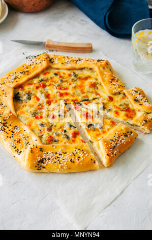 Arabic and middle eastern food concept. Cheese and labneh savory galette with olives on a baking paper. Overhead view. - Stock Photo