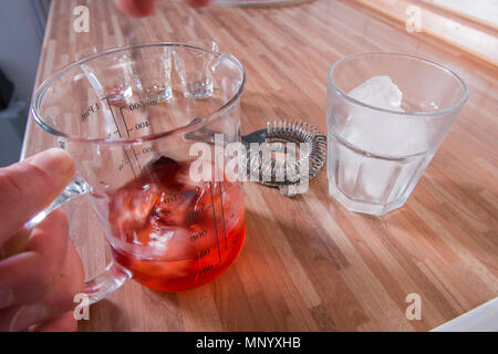 Mixing a negroni cocktail on wooden kitchen worktop - Stock Photo