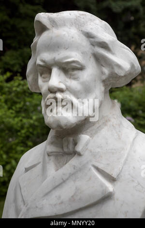 Bust of the Russian composer Mikhail Ivanovich Glinka is set in front of the open stage in the Hermitage Garden in the center of Moscow, Russia - Stock Photo