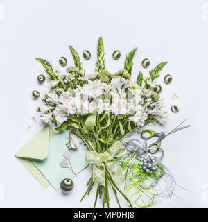 Beautiful festive bouquet  with green flowers on white desk background with envelope and paper card mock up, ribbon and scissors, top view. Holidays g - Stock Photo