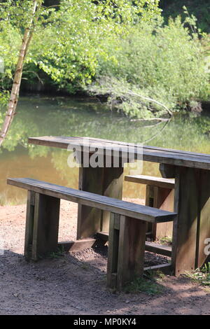 Picnic bench for people to use for sitting and eating on in the woods and park area - Stock Photo