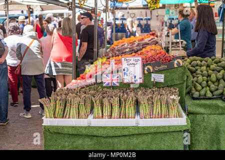 large bunches of fresh Asparagus seen advertised for sale within an open air market in an English city. - Stock Photo