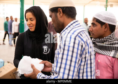Dubai, UAE - May 18, 2018: Volunteers distributing food packages to workers during iftar meal as part of a Ramadan charity drive by local mosque. - Stock Photo