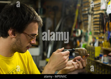 Young artisan pipemaker looking at his own creation - Stock Photo