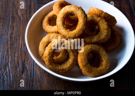 Homemade Crunchy Fried Onion Rings on dark wooden surface. Fast Food. - Stock Photo