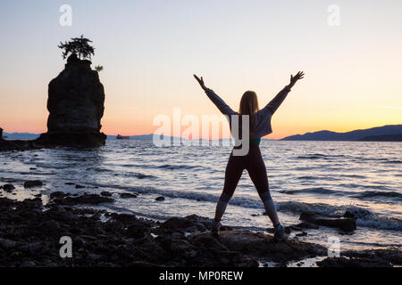 Young Woman on a rocky shore during a vibrant sunset. Taken in Stanley Park, Vancouver, British Columbia, Canada. - Stock Photo