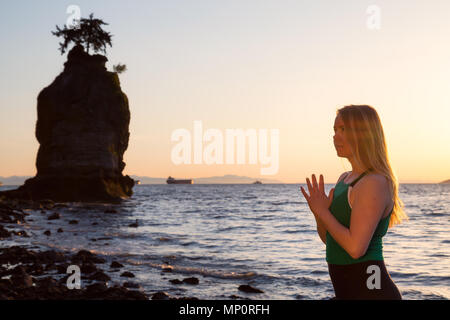 Young Woman holding hands in prayer position during a vibrant sunset. Taken in Stanley Park, Vancouver, British Columbia, Canada. - Stock Photo