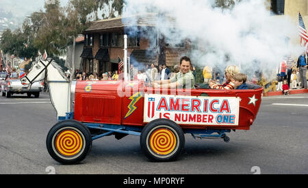 A comical custom-made vehicle that belches smoke and bounces up and down like a bucking horse attracts attention in 1983 during a Fourth of July parade that was celebrating America's annual Independence Day in Laguna Beach, California, USA. Historical photo. - Stock Photo