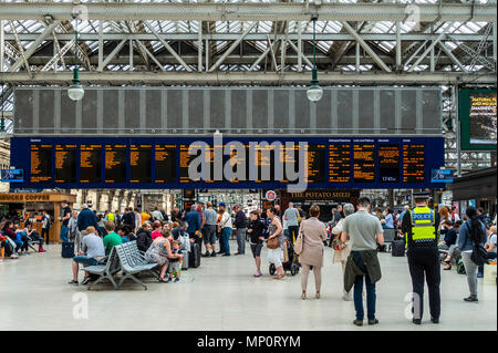 Passengers waiting for trains in front of the main Departures Board in the concourse of Glasgow Central Station, Glasgow, Scotland, UK - Stock Photo