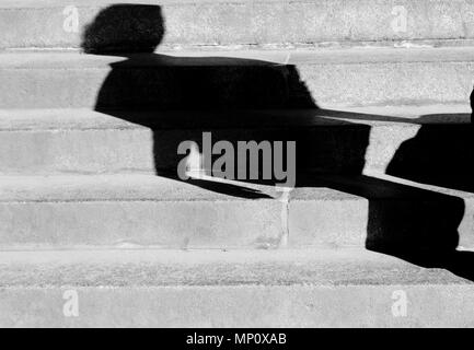 Blurry abstract  broken  shadow of a woman walking alone up the public city stairs in black and white - Stock Photo