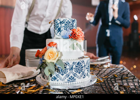 waiter will present at the restaurant. Wedding cake with flowers. Bride and groom cut sweet cake on banquet in restaurant. - Stock Photo