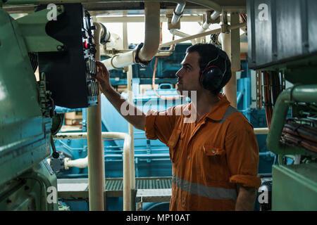 Marine engineer inspecting ship's engine in engine control room - Stock Photo