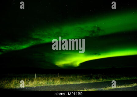 Amazing Northern Lights over the Iceland sky. The bright dancing lights of the Aurora Borealis. Green light in beautiful nightscape. - Stock Photo
