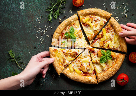 Hot Hawaiian pizza with chicken, pineapple and cheese, hands, taking pieces pizza served with cheese sauce. Delicious traditional Italian pizza.
