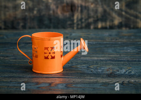 Simple orange metallic watering can on blue wooden background - Stock Photo
