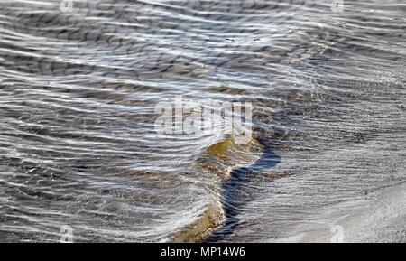 Close up of soft rolling waves on sandy beach - Stock Photo