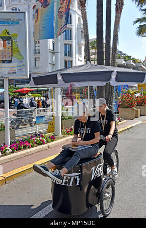 Cannes, France - May 11, 2018:  Unidentified woman distributing Variety magazines to the crowd, and one getting a ride, at the 71st Cannes Film Festiv - Stock Photo