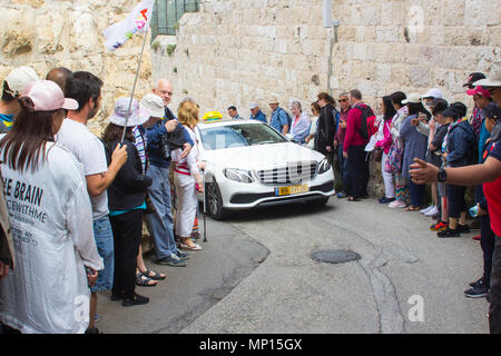 Tourists give way to a taxi cab as it moves slowly up the steep hill of the avenue to the Garden of Gethsemene on the Mount of Olives in Jerusalem - Stock Photo