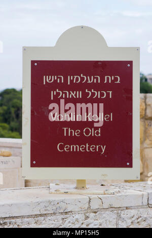 A sign in Hebrew and English mounted on a stone wall at the entrance to The Old  Cemetery on the Mount of Olices in Jerusalem Israel - Stock Photo