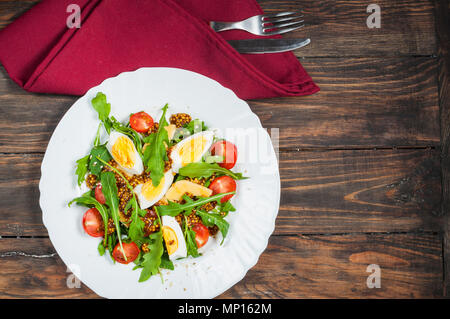 Salad with arugula, cherry tomatoes, eegs and cheese on white ceramic plate over rustic wood background - Stock Photo
