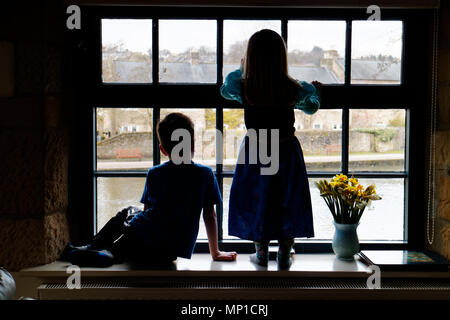 Brother (5 yrs old) and sister (3 yrs old) sat on a window sill, silhouetted against a sash window with the River Wye in Bakewell outside - Stock Photo