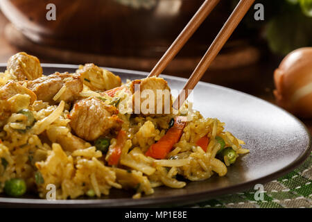 Fried rice nasi goreng with chicken and vegetables on a plate. Indonesian cuisine. - Stock Photo