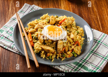 Fried rice nasi goreng with chicken egg and vegetables on a plate. Indonesian cuisine. - Stock Photo