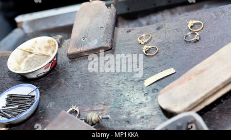 Goldsmith's bench with some golden rings in process - selectived focus - Stock Photo